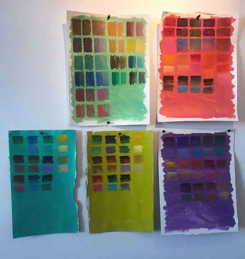 Photography of art studio wall. 5 sheets of colorful paper are pinned to a white wall. Over the bright colors, green/coral/teal/chartreuse/purple, are grids of oil paint colors.