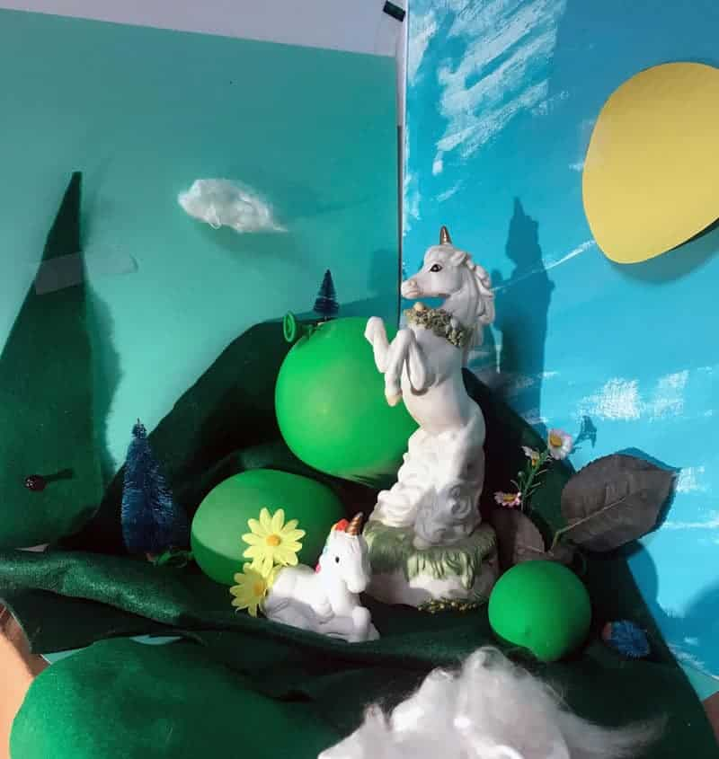Photographs of still life for oil painting. Still life, a square diorama-like space, features blue papers as the sky, green felt and bristle trees and green latex balloons to mimic the ground and mountains. A circle of yellow construction paper is the sun. Cotton and raw silk are fluffy clouds. 2 ceramic unicorn figurines stand amongst the crafted landscape.