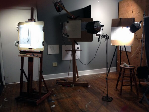 Photograph of drawing art studio. Easels hold drawing boards with spotlights shining on them.